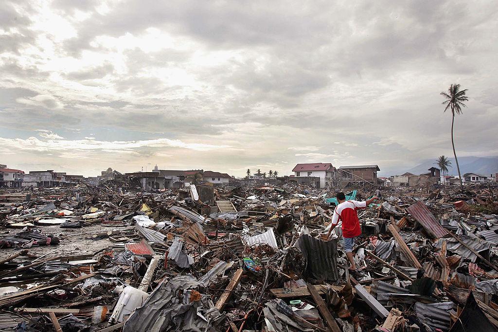 2019年12月26日,在南亞大海嘯15周年之際,人們緬懷當年22萬罹難者。圖為2005年1月10日,在印尼的班達亞齊,一名男子走過毀壞的建築物。(Spencer Platt/Getty Images)