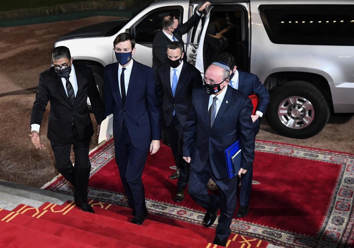 2020年12月22日,美國總統顧問賈里德‧庫什納(Jared Kushner,中)和以色列國家安全顧問梅爾‧本‧沙巴特(Meir Ben Shabbat,右)乘坐首架以色列—摩洛哥直航商業航班抵達摩洛哥首都拉巴特王宮,代表著美國促成猶太國家與阿拉伯國家之間外交正常化協議的最新進展。(FADEL SENNA/AFP via Getty Images)