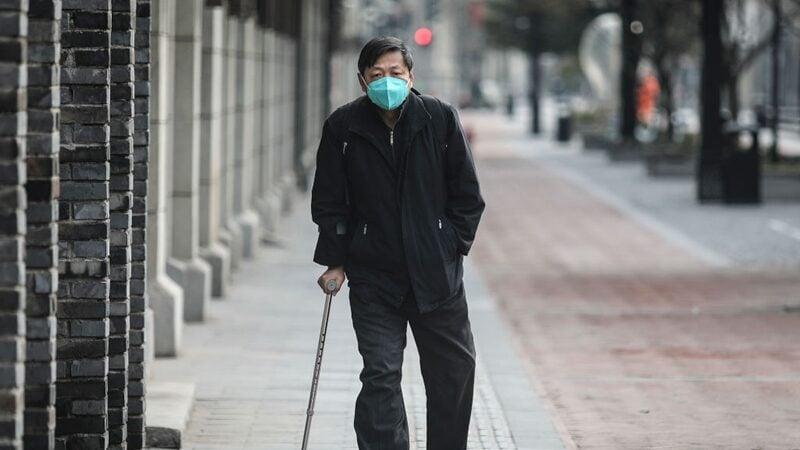 圖為2月8日,一位戴著口罩的武漢男士走在空蕩的大街上 。 (Photo by Getty Images)