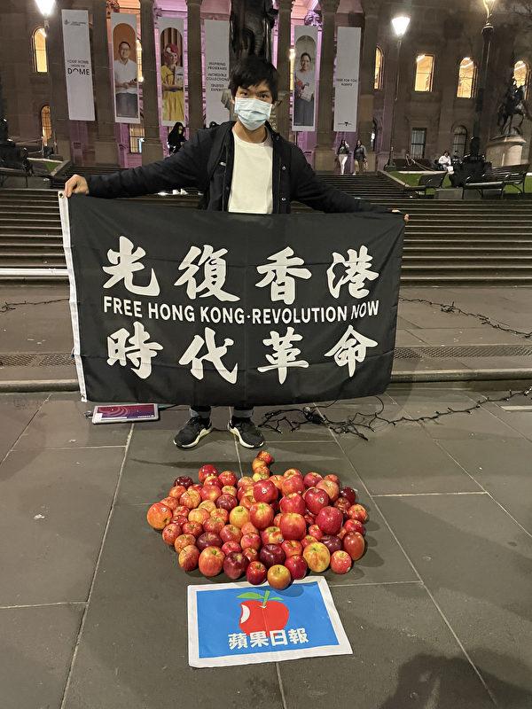 2021年7月1日晚,一位香港小伙手舉「光復香港 時代革命」的標語,聲援《蘋果日報》,表達對恢復香港言論自由的訴求。(周婉晴/大紀元)