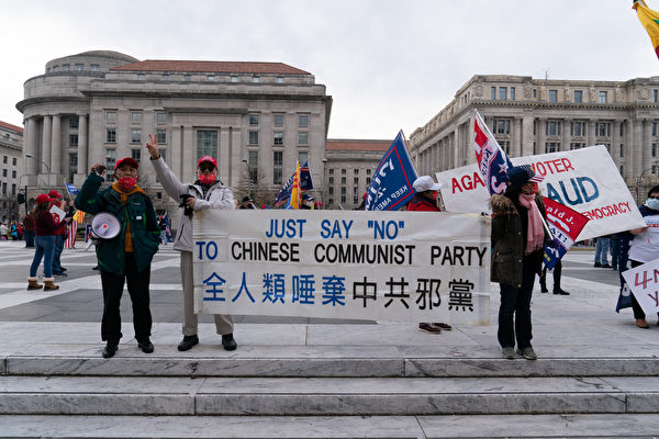 12月12日,華人在華府自由廣場舉橫幅。(石青雲/大紀元)