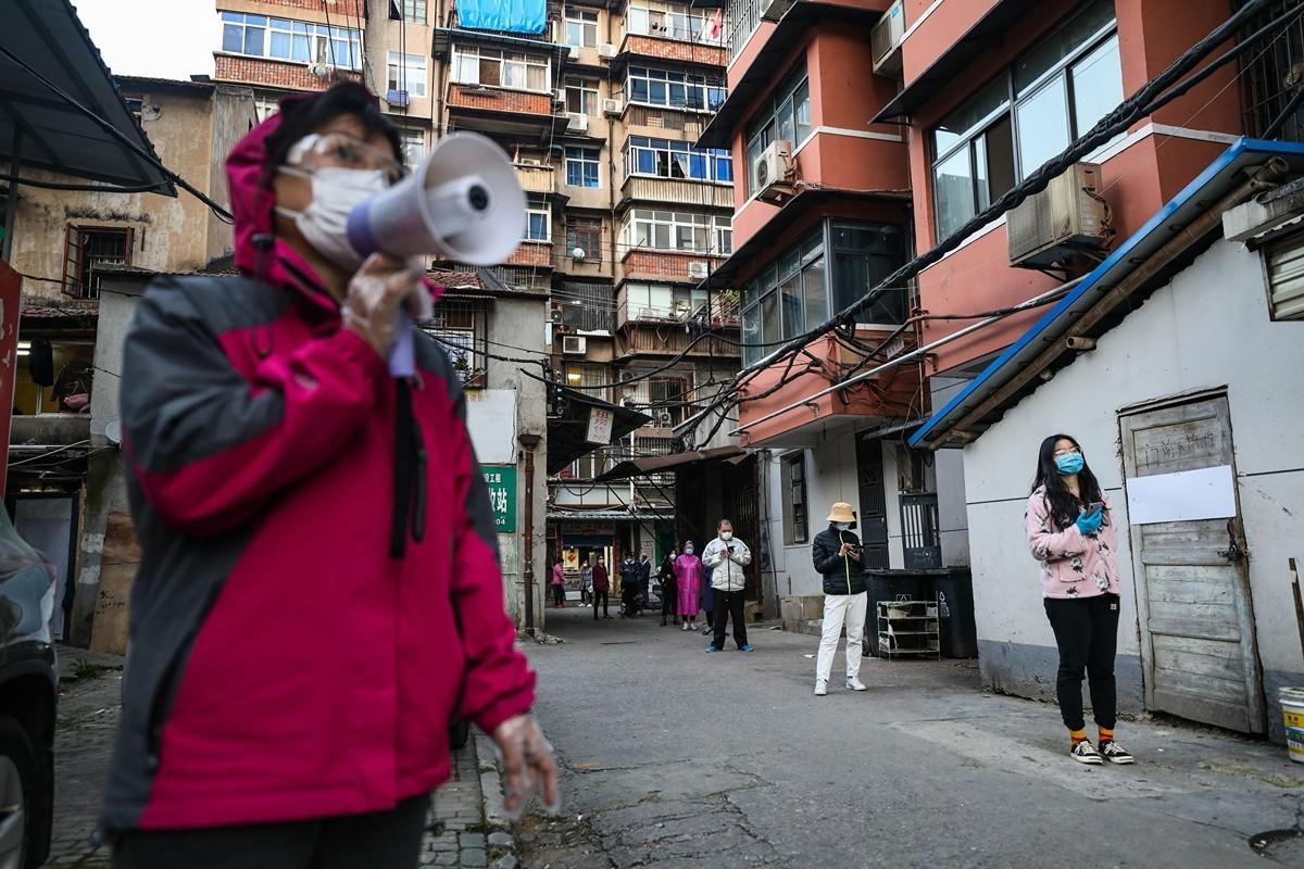 圖為2020年3月18日武漢市居民排隊領取團購的食品。(AFP/Getty Images)
