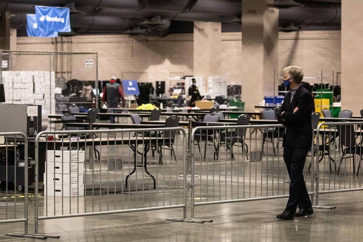 郵寄選票在本次美國大選中造成巨大爭議,外界質疑不合格與遲到選票都被計入,計票時觀察員也無法獲得有意義的權限。圖為11月06日的費城會議中心計票時,一個人從觀察員區域觀看計票過程。(Chris McGrath/Getty Images)