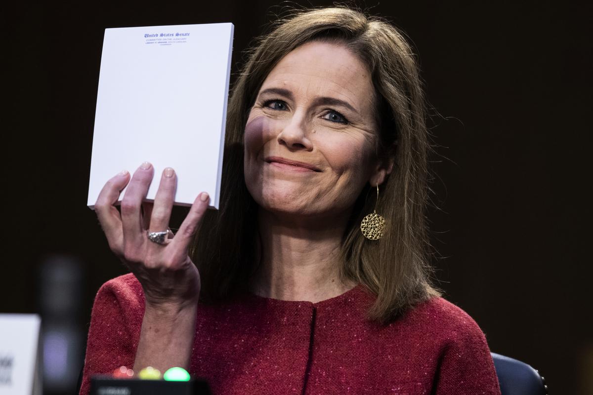 10月13日,在參議院大法官聽證會上,有議員問巴雷特法官是否需要筆記來幫助回答議員提出的問題。巴雷特舉起她面前的一個空記事本,表明她無需筆記協助。(Photo by Tom Williams / POOL / AFP)