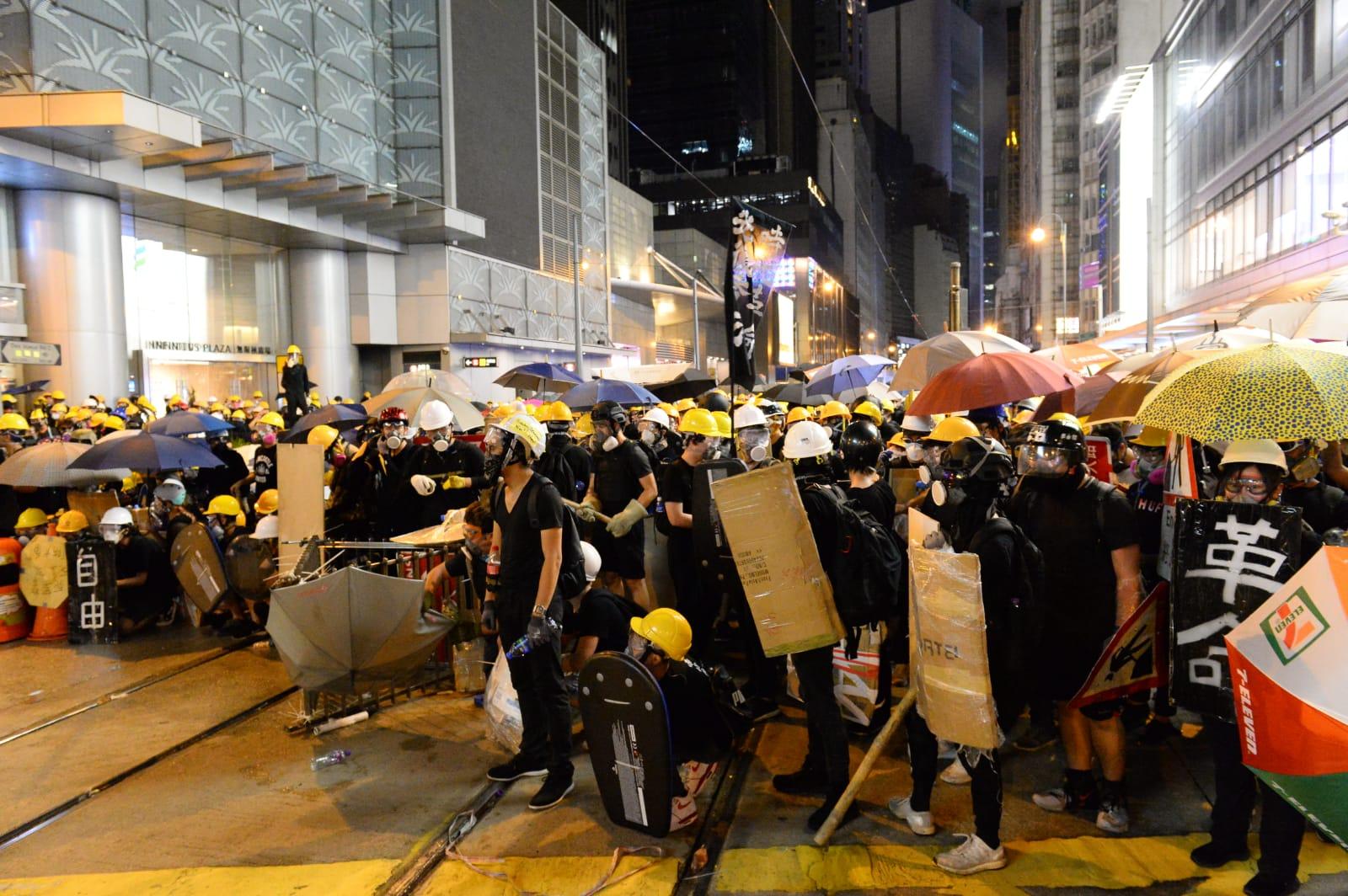 防毒面罩、頭盔、雨傘等成為香港違禁品。圖為2019年7月28日,香港,面對警察頻繁發射橡膠子彈及催淚彈清場,許多香港民眾戴上口罩與頭盔,並以雨傘抵抗。(宋碧龍/大紀元)