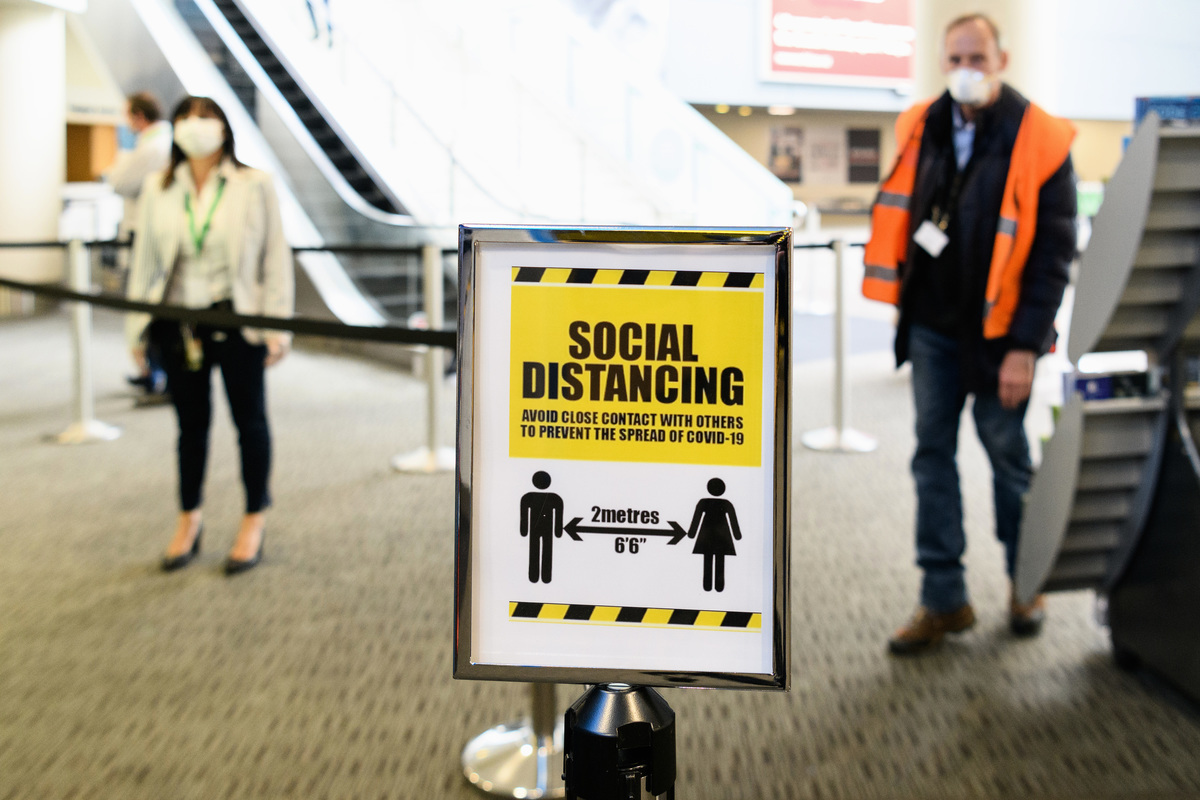 圖為紐西蘭基督城(Christchurch)國際機場的標識牌提醒旅客保持社交距離。(Kai Schwoerer/Getty Images)