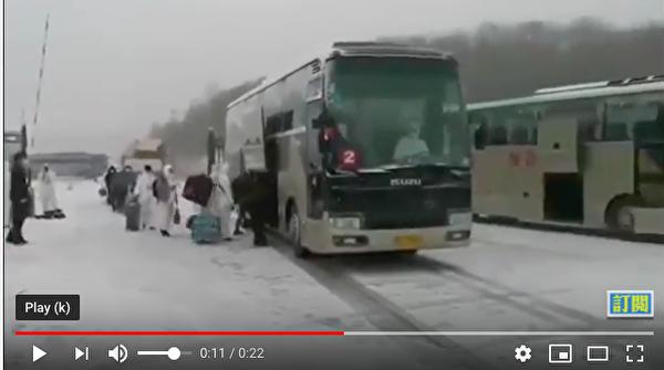 從俄羅斯入境中國的華人在大雪紛飛中,被從俄方客車轉運到中方客車,中共派遣了武警部隊。(影片截圖)