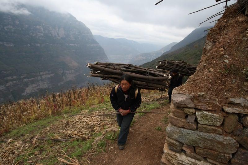 近日李克強曝光六億人月收入千元。而所謂扶貧被指「走形式,假把式」。圖為示意圖,一位四川的農民背著木柴走在山區中。(Getty Images)