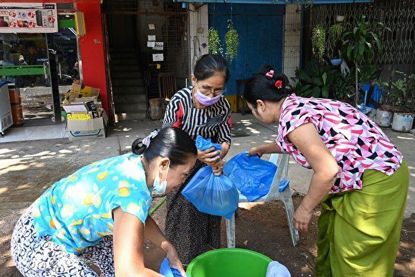 2021年3月8日,仰光民眾在街頭抗議軍事政變活動中,一些婦女用塑料裝水為抗議者準備應對武警發射的催淚彈。(STR/AFP via Getty Images)
