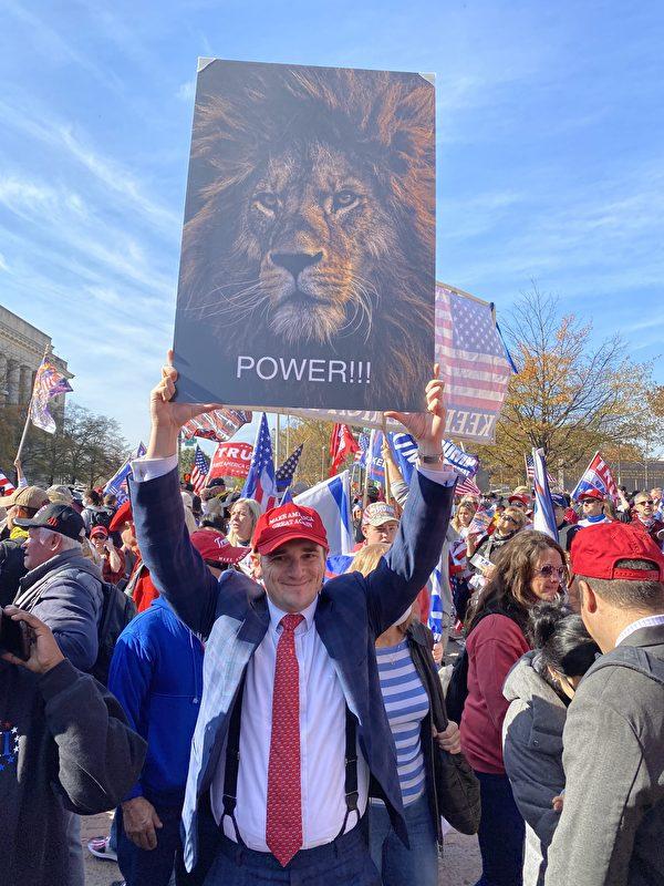 2020年11月14日,美國各州民眾在美國首都華盛頓DC舉行挺特朗普大遊行,一位民眾舉著《獅子王》的海報。(施萍/大紀元)