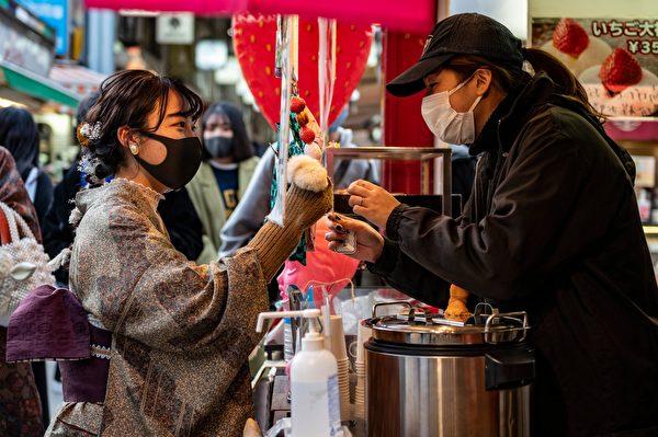 2020年12月29日,日本東京淺草寺附近,購買食物的顧客和店員都戴著口罩。(PHILIP FONG/AFP via Getty Images)