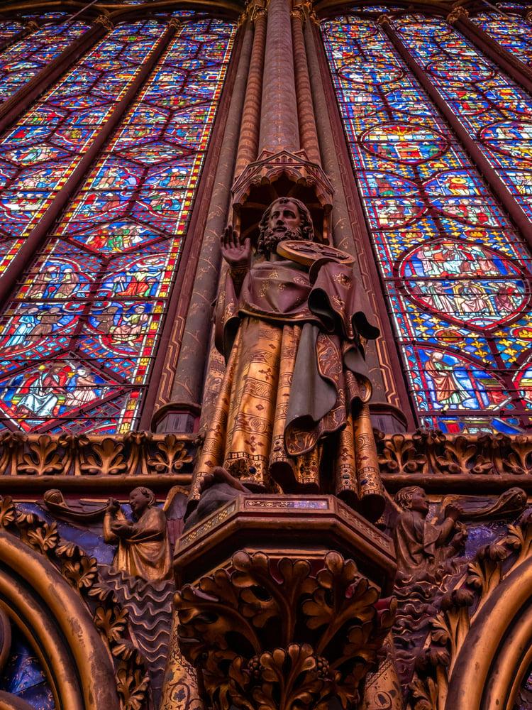 耶穌十二門徒之一的雕像,下面是手持香爐的天使。(Shutterstock)