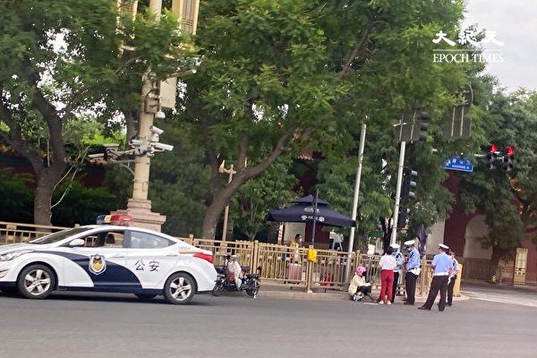 2020年6月22日,北京警察在查過路人的身份證。(大紀元)