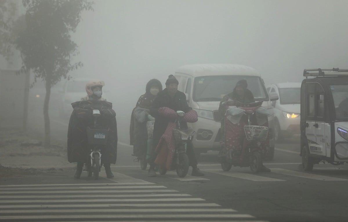 陰霾大面積持續多日籠罩大陸華北、黃淮、江漢等地區。圖為12月7日,人們在陰霾籠罩的山東菏澤曹縣街頭騎行。(大紀元資料室)
