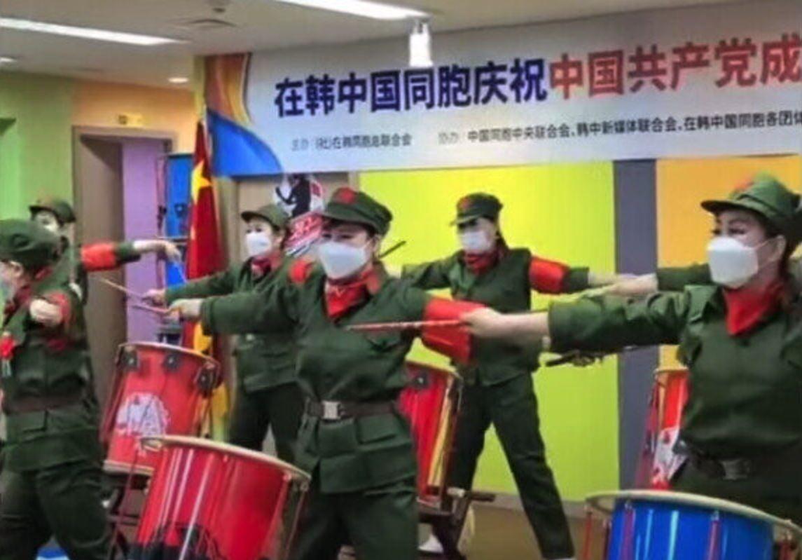 身穿解放軍服裝的活動參與者敲鼓的場面。(在韓中國同胞TV影片截圖)
