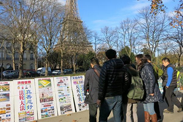 大陸遊客在巴黎艾菲爾鐵塔景點觀看法輪功真相展板。(大紀元)