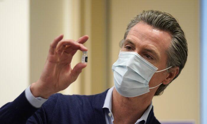 2020年12月14日,加州州長加文‧紐森(Gavin Newsom)在洛杉磯的凱撒醫療中心,拿起一小瓶新的中共病毒疫苗。(Jae C. Hong/Pool/Getty Images)