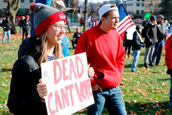 2020年11月14日,在密歇根蘭辛,民眾聚集在州議會大廈外,抗議大選舞弊,要求制止竊選。圖為一位民眾舉著寫有「死者不能投票」的展板表達抗議。(JEFF KOWALSKY/AFP via Getty Images)