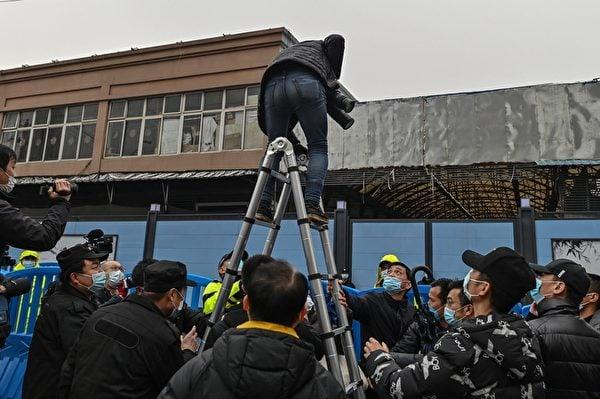 1月31日,世界衛生組織(WHO)專家小組到武漢已封閉的華南海鮮批發市場時,警衛人員監視著站上梯子給世衛專家拍照的攝影記者。(HECTOR RETAMAL/AFP via Getty Images)