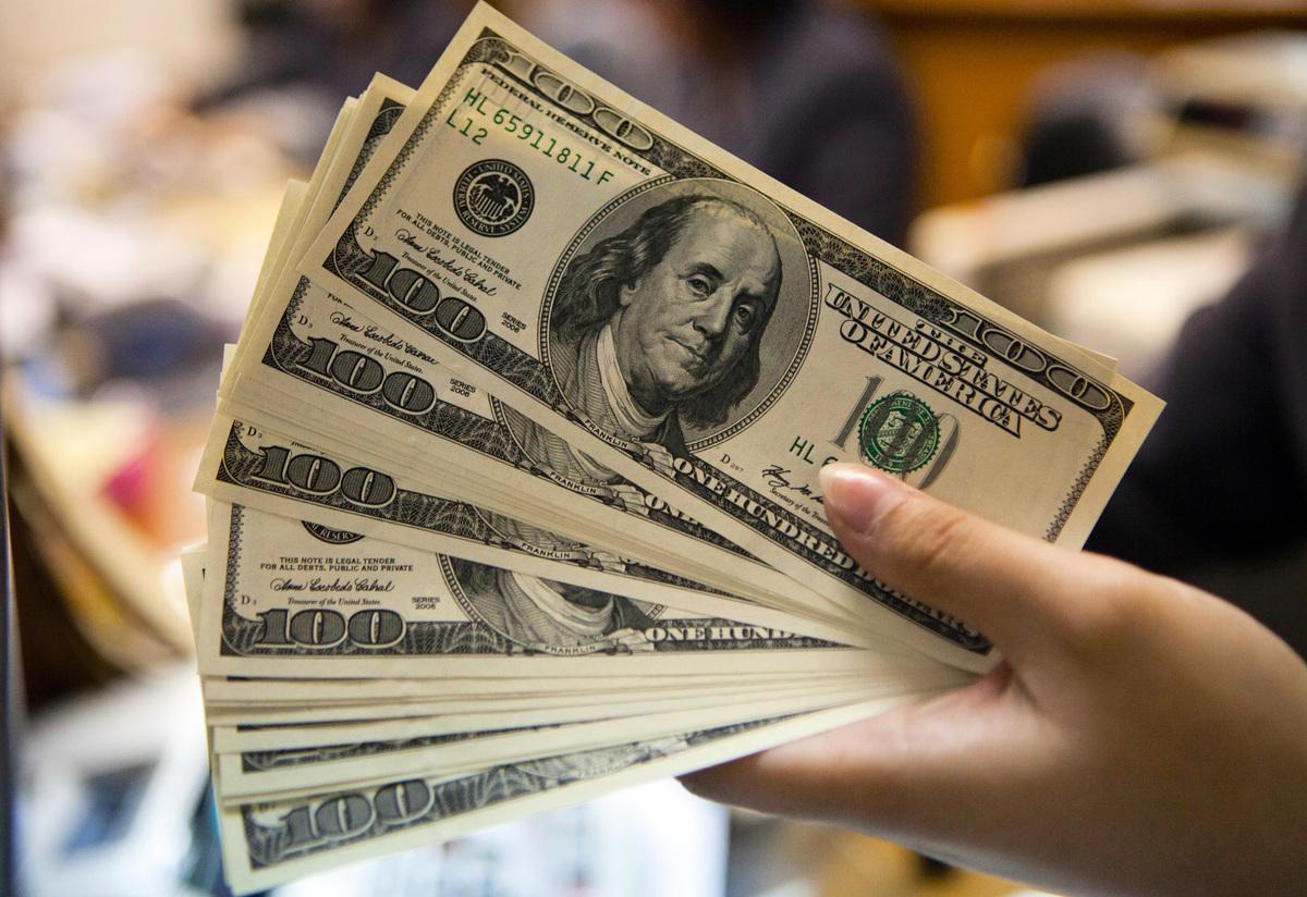 美國上周首次申請失業救濟金人數下降到78.7萬人,創疫情爆發以來新低。圖為100美元紙幣。(OSCAR SIAGIAN/AFP/GettyImages)