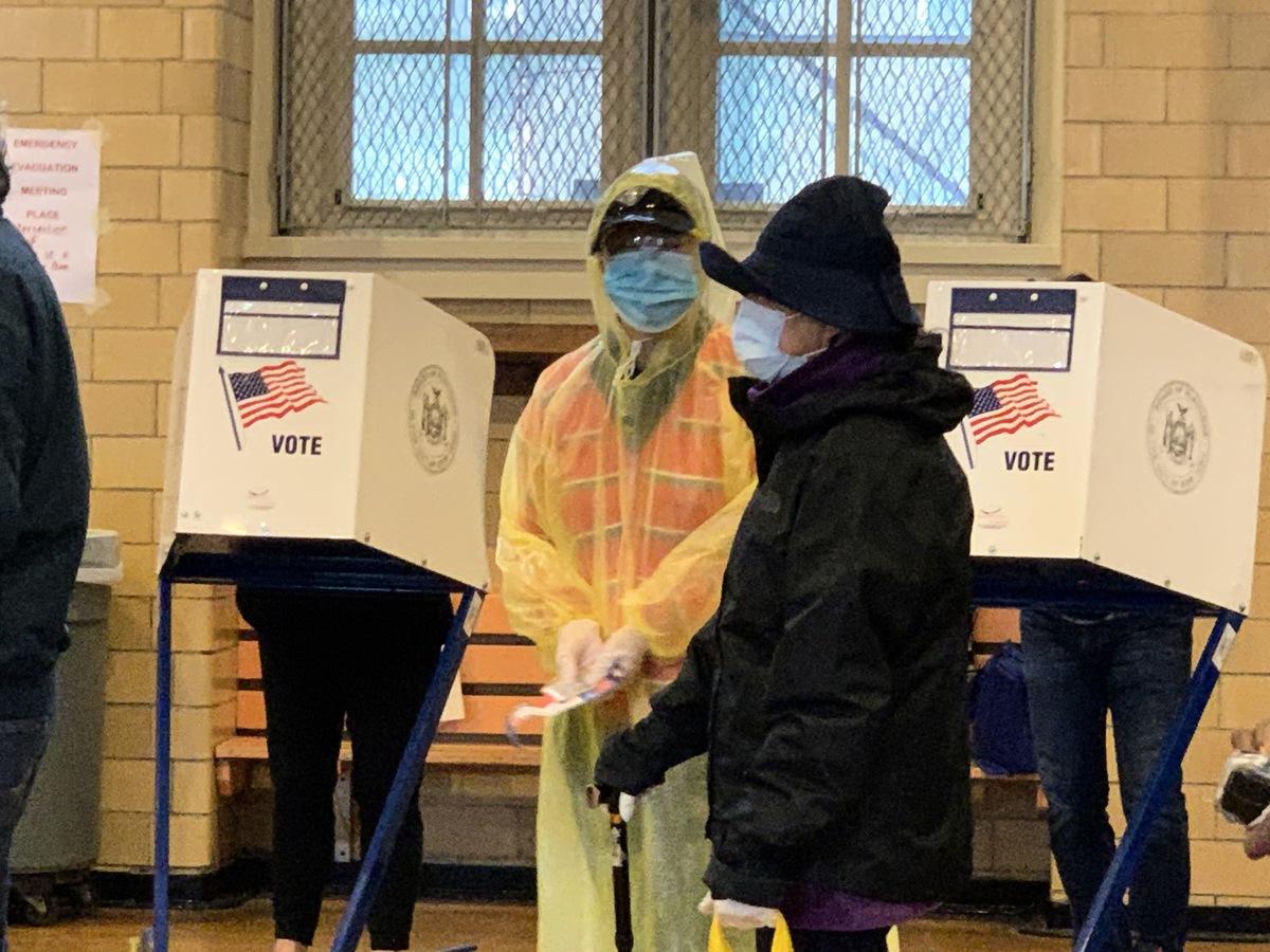 有選民穿上雨衣作為防護服前去投票。(林丹/大紀元)