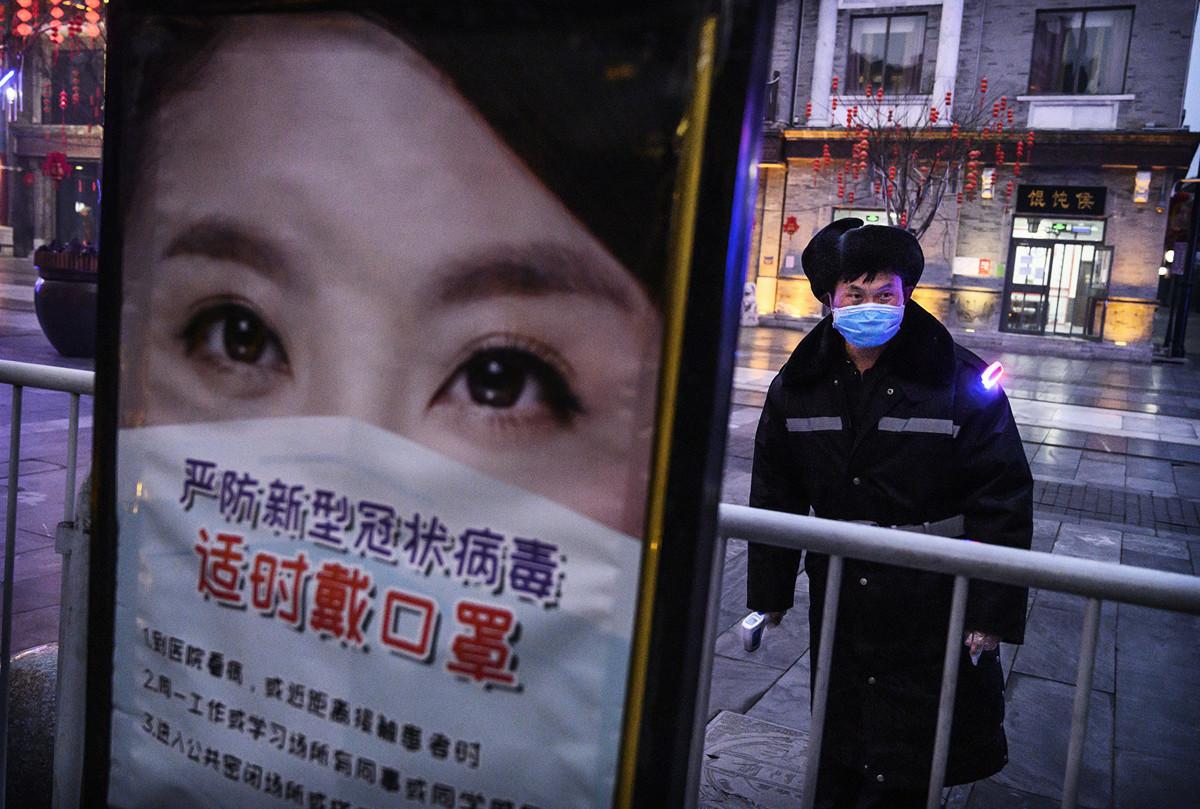 中共病毒持續肆虐,大陸疾控權威專家指,返程流動人口使疫情有再惡化的風險。圖為2月12日, 北京一名保安在等待給過往的人測體溫。(Kevin Frayer/Getty Images)