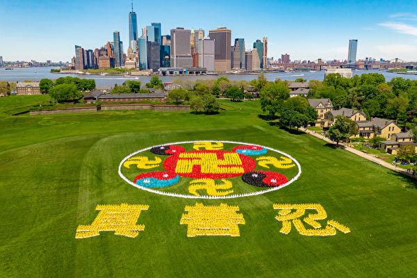 2019年5月18日,來自全球的部份法輪功學員匯聚紐約,在曼哈頓下城摩天大樓群對面的總督島,排出巨型「法輪圖形」和「真善忍」三個大字,慶祝世界法輪大法日。(新唐人電視台)