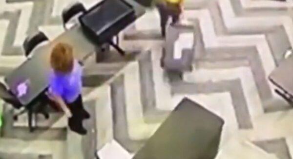 佐治亞州州立農場體育館監控錄影截圖。有人從桌子底下拉出一箱子選票,箱子不知何時何人放置。(新唐人影片擷圖)