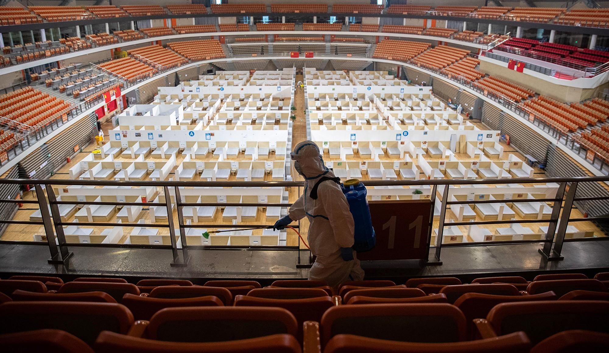 圖為2020年3月8日在武漢體育館改造的方艙醫院裏,一名工作人員噴灑消毒劑。(AFP/Getty Images)