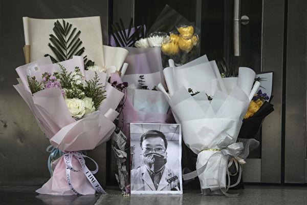 圖為2021年2月7日,湖北武漢市中心醫院外,民眾放置李文亮醫師的遺照及鮮花表達哀悼。(Getty Images)