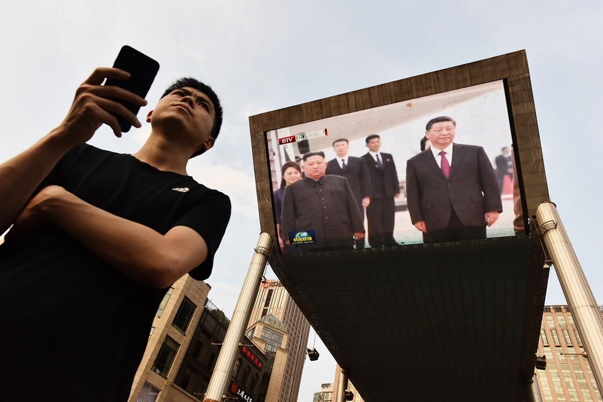 習近平6月20日~21日高調訪問北韓。圖為一男子在北京商場外影屏前等待的士。 (GREG BAKER/AFP/Getty Images)