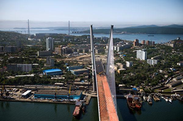 2001年,江澤民與普京私下簽署《中俄和睦友好合作條約》,承認海參崴及鄰近遠東地區「永遠」不再為中國的領土。圖為海參崴的金角灣大橋。(MARTIN BUREAU/AFP)