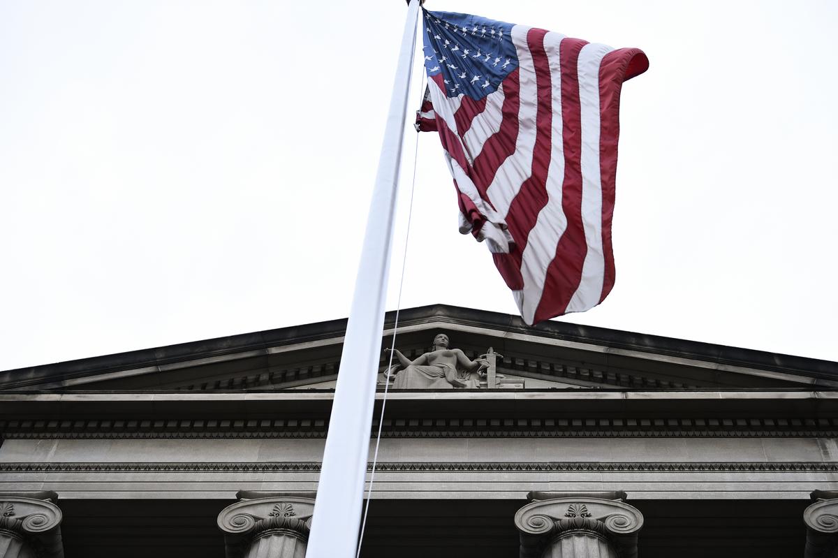 美國聯邦政府打擊中共國家主導的竊取知識產權行為,除了通過貿易談判要求中共結構改革外,還有多項政策工具,其中一張王牌是美國的司法系統。圖為一面美國國旗在司法部大樓外飄揚。(Brendan SMIALOWSKI / AFP)