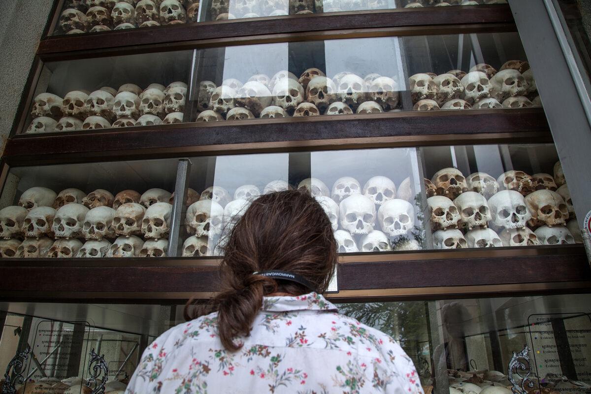 一名年輕的柬埔寨婦女注視著Choeung Ek Killing Fields的主要佛塔,裏面充滿了成千上萬在2014年8月6日在柬埔寨金邊的波爾布特政權期間喪生的頭骨。(Omar Havana/Getty Images)