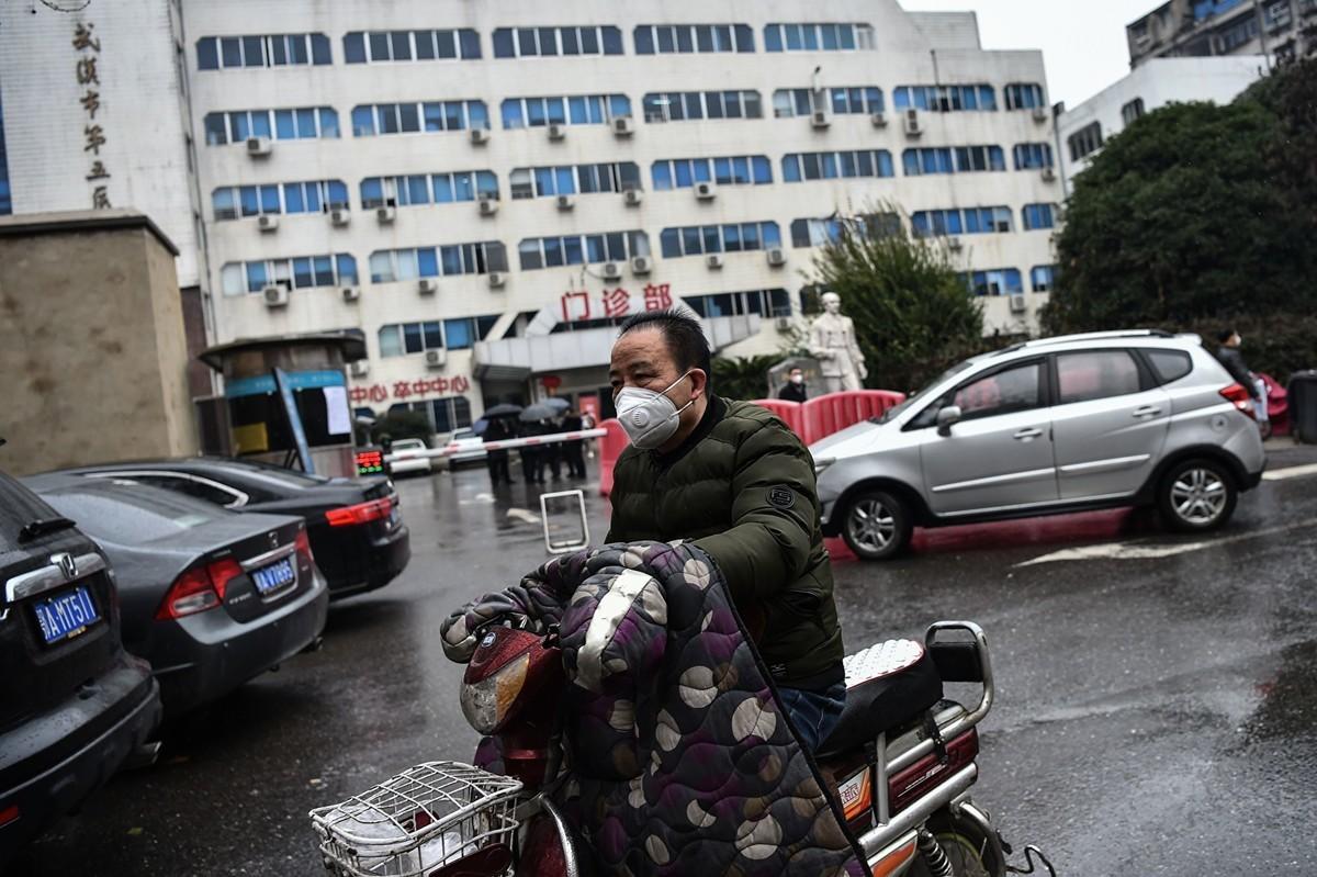 圖為2020年1月24日,一名戴著口罩的男子戴著口罩開車經過湖北省武漢第五醫院門診前。(HECTOR RETAMAL/AFP via Getty Images)