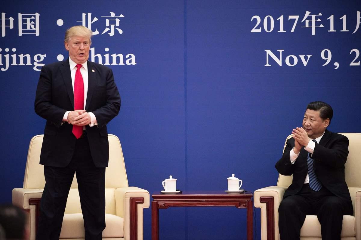 2017年11月9日,美國總統特朗普(左)訪問北京,與習近平(右)共同參加一個企業家論壇活動。(Nicolas Asfouri/AFP via Getty Images)