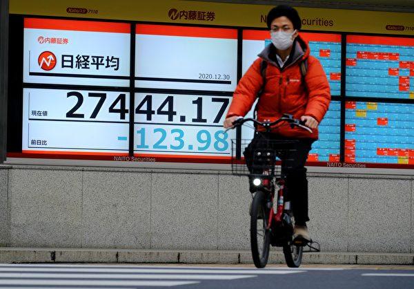 2020年12月30日,日本東京,一位騎單車的市民戴著口罩。(KAZUHIRO NOGI/AFP via Getty Images)