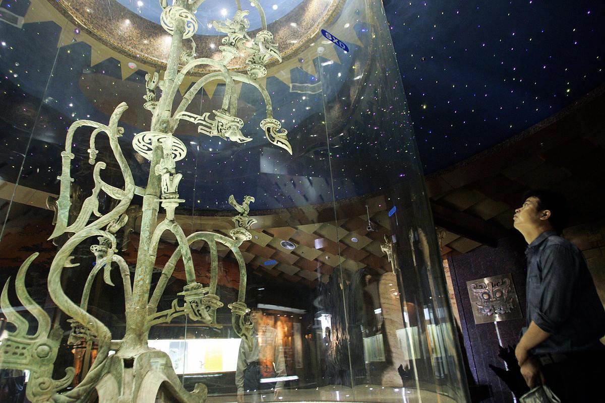 圖為2005年5月28日,遊客在四川廣漢市的三星堆博物館,觀看展出的一棵青銅樹文物。文物的造型與中原文化大不相同。(Liu Jin/AFP via Getty Images)