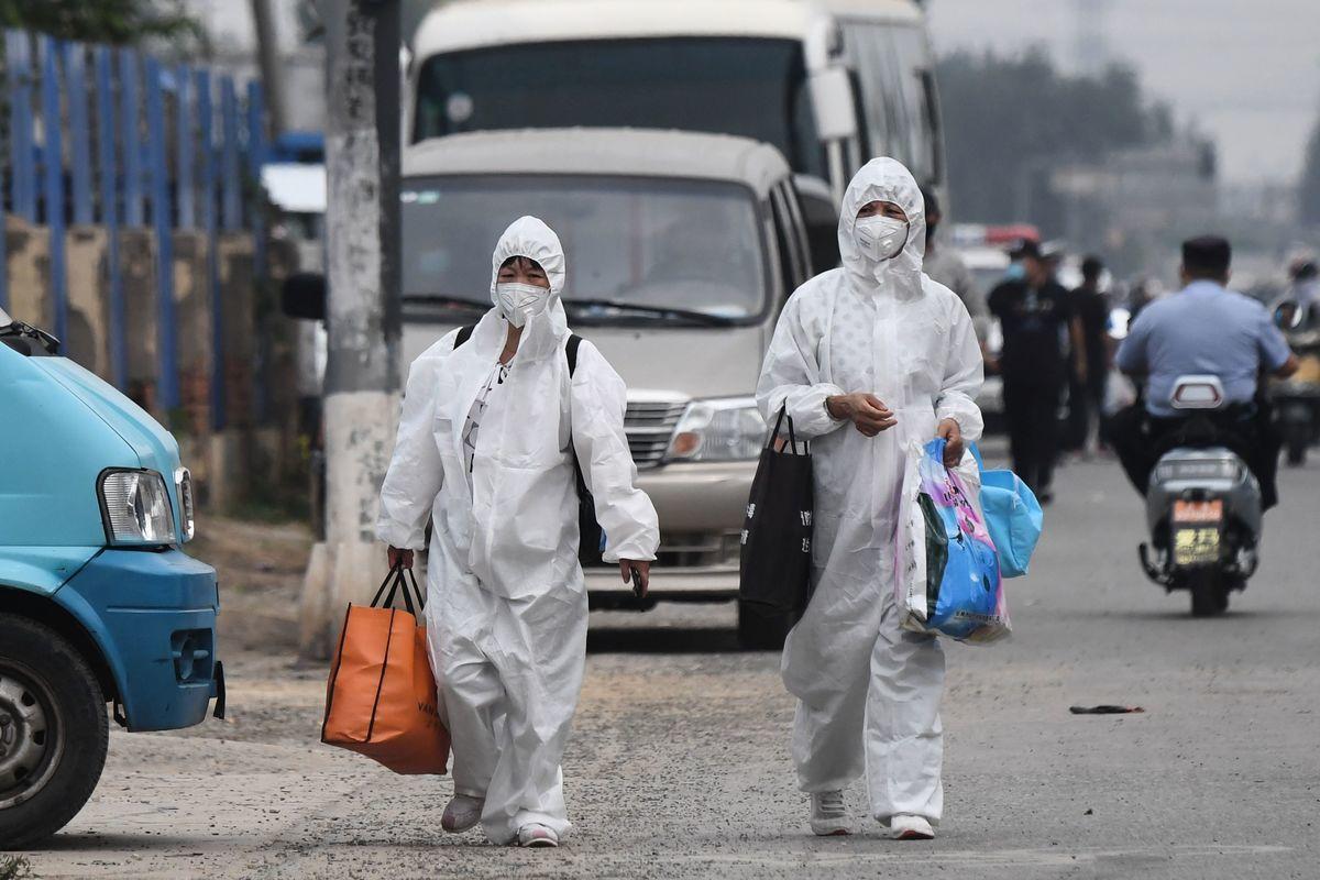 圖為6月13日,兩女士全身穿防護服走在新發地附近街道。(GREG BAKER/AFP via Getty Images)