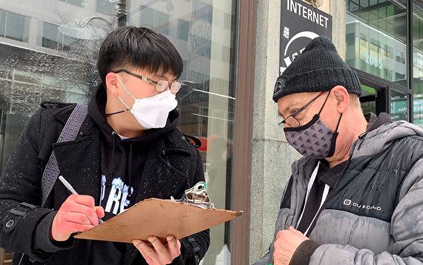 南韓青年(左)在呼籲制裁中共的徵簽信上簽字,並表示希望自己是遊行隊伍中的一分子。(大紀元)