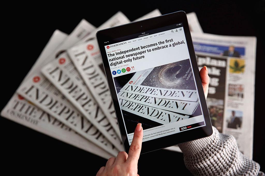 圖為2016年2月12日,在停止印刷前一個月的英國「星期日獨立報」,其網站顯示在iPad上,後面是印刷版報紙。(Dan Kitwood/Getty Images)