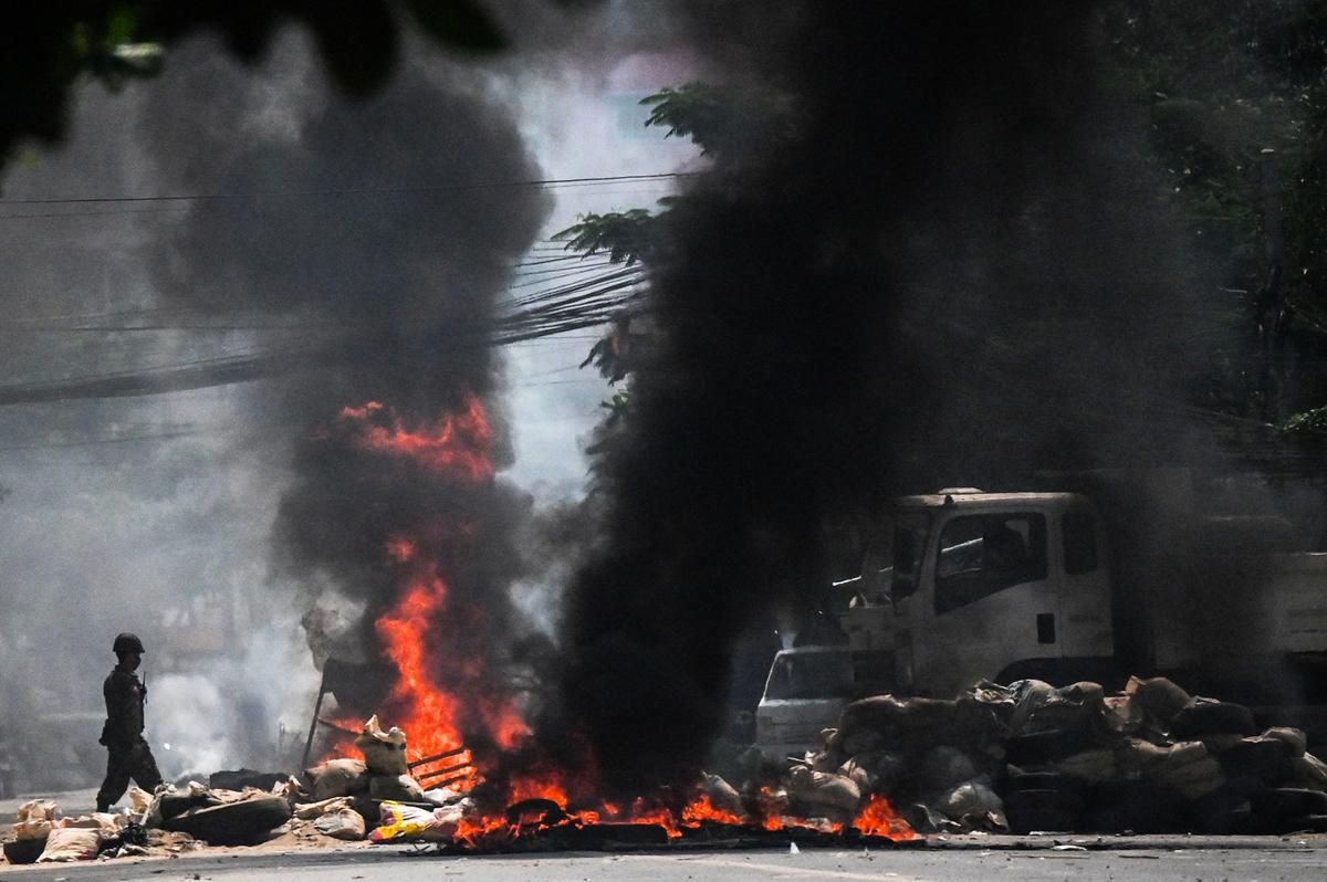 2021年3月19日,緬甸軍隊放火燒掉仰光抗議者設置的路障。該國2月21日發生軍事政變,昂山素姬(Aung San Suu Kyi)的民選政府被推翻,全國性抗議活動自此掀起,軍方鎮壓行動不斷升級。(STR/AFP via Getty Images)