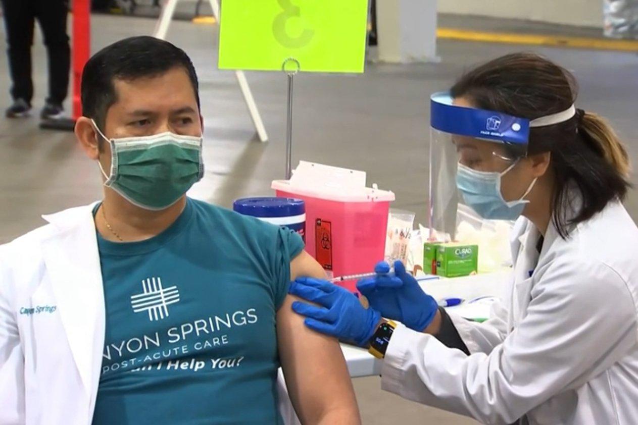 2020年12月17日,在聖塔克拉拉縣聖荷西市的露天市集內,護士為醫護人員羅佩雷斯(Cliff Roperez)(左)注射中共病毒疫苗。(聖塔克拉拉縣衛生局提供)