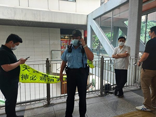 白衣男子4月7日在香港灣仔天橋扯下法輪功學員的標語,被員警拘捕。(法輪功學員周小姐提供)