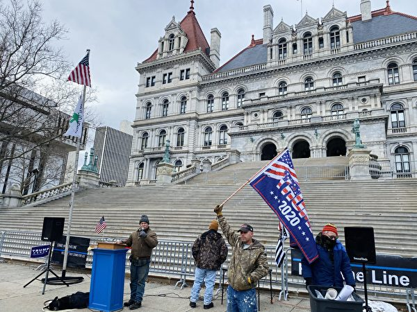 12月26日,紐約州首府奧爾巴尼(Albany)州府議會大廈(East Capitol Park)前,多位民眾揭露中共罪行,打旗者為John。(大紀元/李桂秀)
