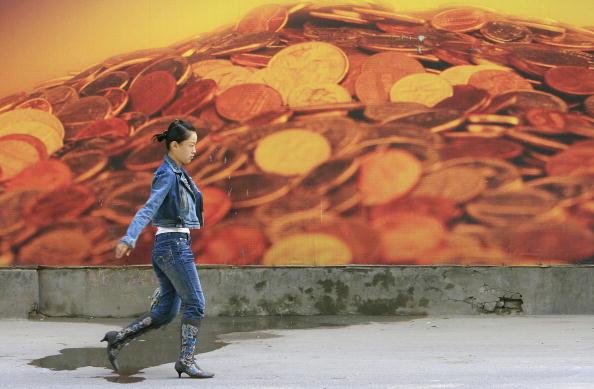 中國大陸社會被指成為一充滿陷阱的社會,中共的銀行業及類金融行業,與中共權貴、黑惡勢力、司法機關相勾結,共同收割民間的財富。圖為2006年10月19日,一名女士經過北京一個印有錢幣的廣告牌。(FREDERIC J.BROWN/AFP/Getty Images)