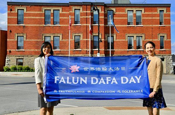 加拿大法輪大法協會發言人戴工羽(左)與法輪功學員Daniella Wollensak(右)慶祝世界法輪大法日。(任建/大紀元)