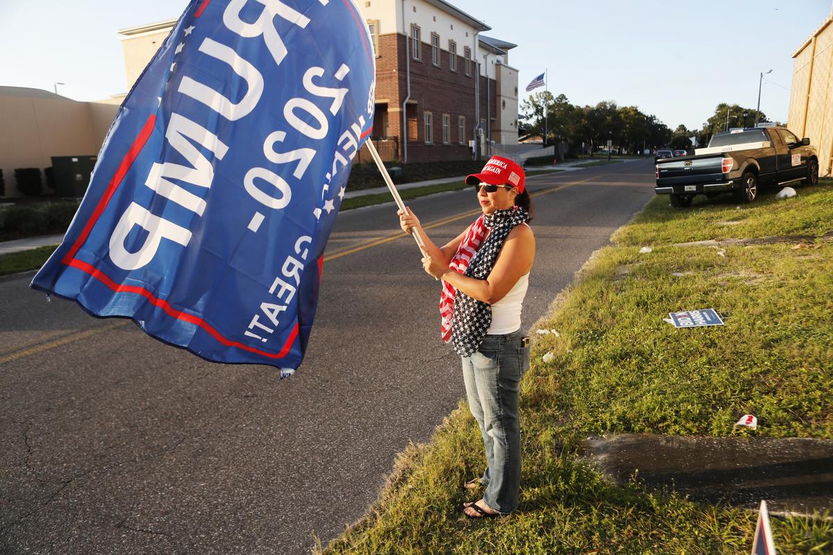 2020年11月3日,美國佛羅里達州坦帕市(Tampa),特朗普總統的支持者 在一間位於公共圖書館的投票所附近揮舞著競選旗幟。(Octavio Jones/Getty Images)