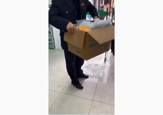 上海市民拍下影片——一名市場監管人員從藥房拿走一箱口罩,而老百姓被限制一次買兩包,而且很多天買不到。(影片截圖)