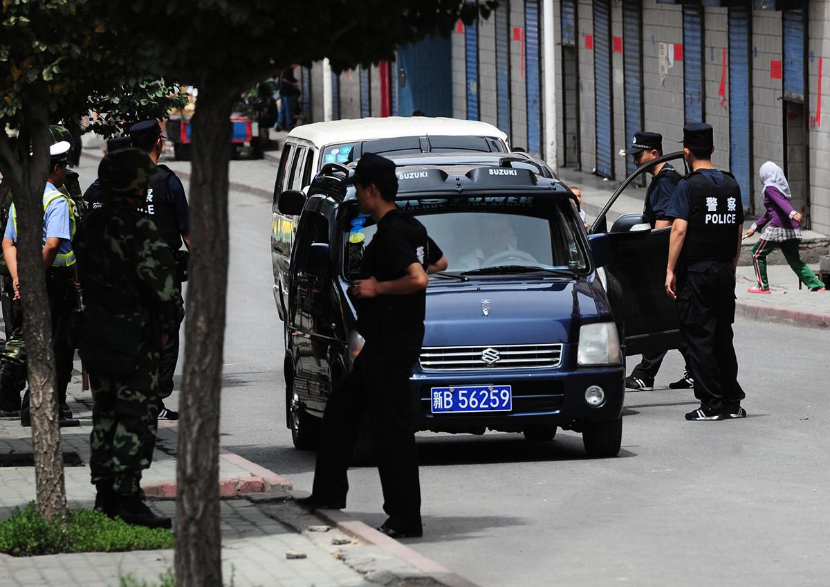 英國《衛報》報道說,中共警察在新疆海關秘密地把監視app安裝在遊客的手機上。圖為2009年7月17日,在新疆烏魯木齊街頭盤查的警察。(FREDERIC J. BROWN/AFP/Getty Images)